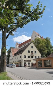 Bavaria, Germany - August 16, 2011: View of Kemptener Street with tree in blurred foreground and houses and view of the High Castle in the urban center of the city of Fussen on a sunny day