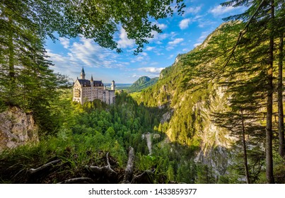 Bavaria, Germany. Fairytale Neuschwanstein Castle in Bavarian Alps mountains. Picturesque view from green forest trees, lake and sunrise sky with clouds. Famous landmark and touristic travel.