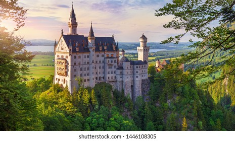 Bavaria, Germany. Fairytale Neuschwanstein Castle in Bavarian Alps mountains. Picturesque view at green forest trees, lake and sunrise sky with clouds. Famous landmark and touristic travel.