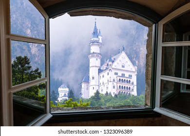 Bavaria, Germany - May 15, 2017: View through old wooden window of Neuschwanstein Castle Fairy Tale Castle Palace commissioned by Mad King Ludwig II of Bavaria of Germany.