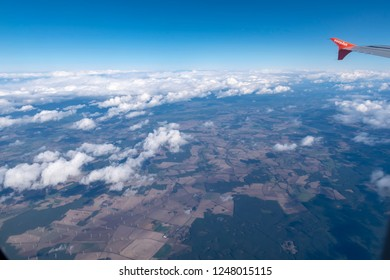 Bavaria, Germany - October 3, 2018: View from an airplane on the wing, the beautiful white clouds and fields with wind turbines on the ground.