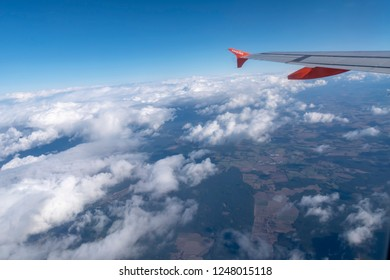 Bavaria, Germany - October 3, 2018: View from a plane to the wing, the beautiful white clouds and fields on the ground.