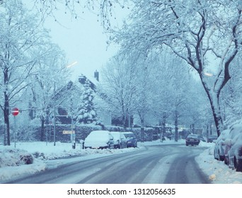 Bavaria,city residential street under a  winter snow fall, landscape and parked cars covered by snow