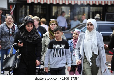 Würzburg, Bavaria/Germany- 05/20/2018: A group of Muslim women and children stroll through Wurzburg's city center.