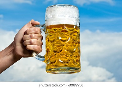 A Bavarian beer held against a blue and white sky