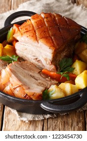 Bavarian beer roasted pork, also known as Bayerischer Schweinebraten or Krustenbraten with vegetables close-up in a frying pan. vertical