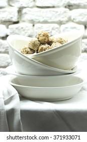 Bavarian bread dumplings in antique white bowls on white linen front of white wall
