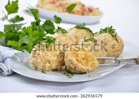 Bavarian bread dumplings served on a white platter, garnished with parsley, sauerkraut with bacon in the background