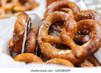 Bavarian delicious freshly baked and freshly prepared homemade soft pretzel lying among pretzels, in the background a different gravy. Close up pretzel salt selective focus