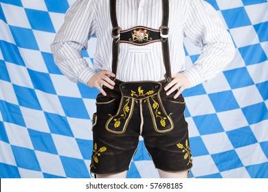 Bavarian man with black Oktoberfest leather pants (Lederhose). In background is Bavarian flag visible.