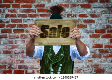 bavarian man in front of brick wall holding a sign with the word Sale
