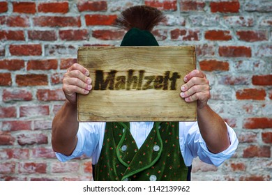 bavarian man in front of brick wall holding sign with the german word for Good Appetite