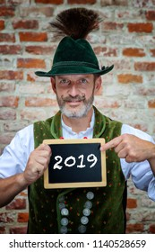 bavarian man holding black board with the number 2019 on it