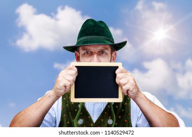 bavarian man holding a blackboard  outdoors with blue sky