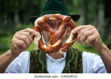 bavarian man holding a pretzel in front of his face outdoors