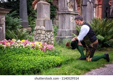 bavarian man kneeling in front of a grave