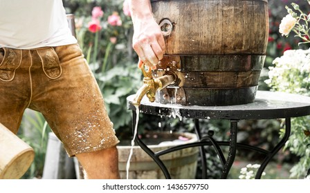 Bavarian man in leather trousers stabs a wooden barrel of beer in the garden and enjoys the first sip