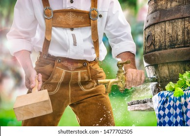 Bavarian man in leather trousers taps a wooden barrel of beer in the garden. Background for Oktoberfest, folk or beer festival