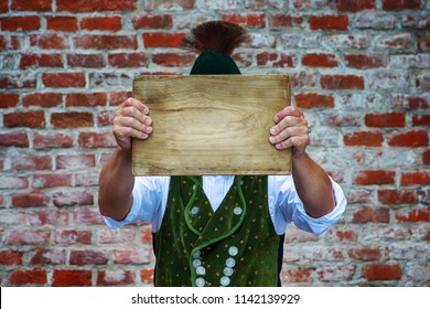 bavarian man outdoors holding a wooden plank in front of his head