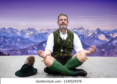bavarian man sitting on front of mountain panorama and meditating