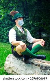 Bayerischer Mann auf Baumstumpf mit Schutzmaske