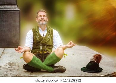 bavarian man sitting outddors on wall and meditating