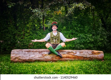 bavarian man sitting outdoors on tree stump and meditating