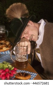 bavarian man sitting at table and is drunk at Oktoberfest