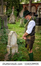 bavarian man standing in front of a grave