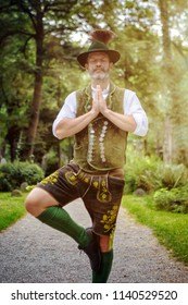 bavarian man standing outdoors in yoga position and meditating