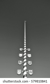 A Bavarian maypole against a blue sky and sunshine in Black and White