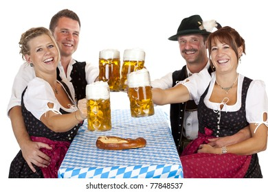 Bavarian men and women toast with Oktoberfest beer stein. Isolated on white background.