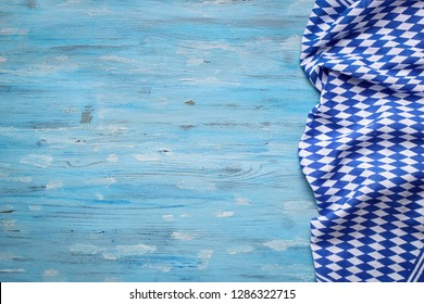 Bavarian napkin from right side of turquoise wooden background. Oktoberfest background concept