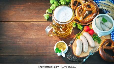 Bavarian sausages with pretzels, sweet mustard and beer mug on rustic wooden table. Oktoberfest menu
