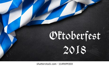 "bavarian tablecloth on slate background with the slogan ""Oktoberfest 2018"""