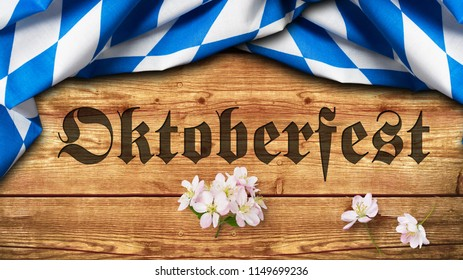 "bavarian tablecloth on wooden background and a chalkboard with the slogan ""Oktoberfest"""