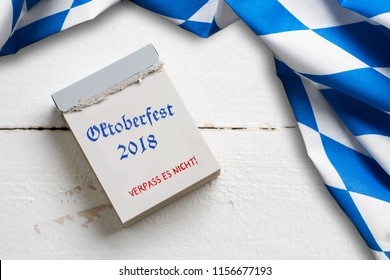 "bavarian tablecloth on wooden background and a tear-off calendar with the slogan ""Oktoberfest 2018"""