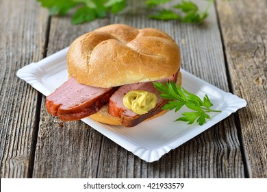 Bavarian takeaway food: A crispy wheat roll with baked meat loaf and mustard on a paper plate