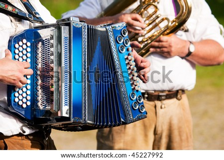 Bavarian traditional band with accordion and tuba playing marching music, only hands of musicians to be seen