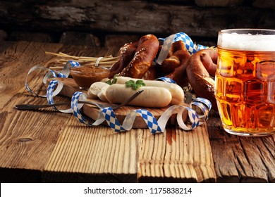 Bavarian veal sausage breakfast with sausages, soft pretzel and mild mustard on wooden board from Germany.