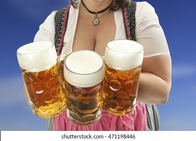 Bavarian Waitress holding Oktoberfest Beer in front of her cleavage with a blue cloudy sky in the background