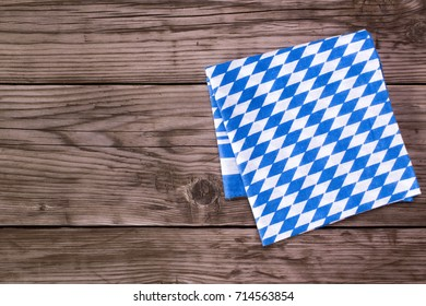 Bavarian white and blue napkin on old wooden table. Oktoberfest background
