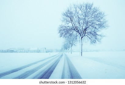 Bavarian winter landscape with heavy snow fall: fog and snow over a  provincial road,  houses and trees