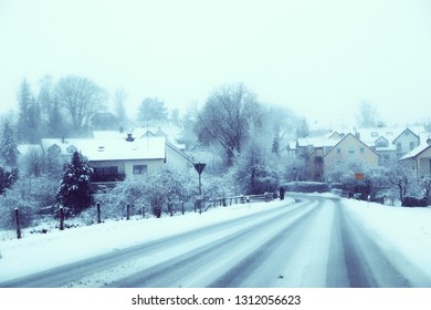 Bavarian winter landscape: provincial road,  houses and trees with fog and snow