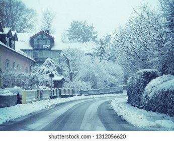 Bavarian winter snow fall landscape: provincial road,  houses and trees with fog and snow