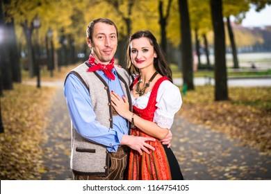 Bavarin Germans in Dirndl and Lederhose, leant against each other
