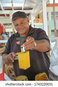 Bavaro, Dominican Republic - 17 Jan 2018: Man peeling a pineapple with a cutter, making a fresh, healthy, raw juice right on the beach. Focus on the hand holding the pineapple. Copy space. Vertical