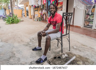 Bavaro. Dominican Republic. December 9, 2020. A young, cheerful Haitian sits against the backdrop of paintings for sale.