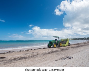 BAVARO, PUNTA CANA, DOMINICAN REPUBLIC - 24 JANUARY 2019: Cleaning sargassum algae on tropical coastline by tractor with Barber Surf Rake. Caribbean ecology problem