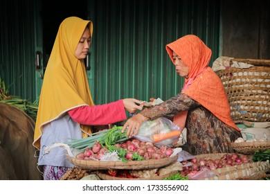 Bawang, Jawa Tengah, Indonesia - May 14 2020  The vegetable seller is arranging his wares